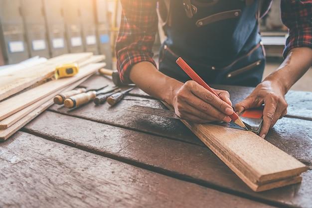 Carpentiere che lavora con l'attrezzatura sulla tavola di legno nel negozio di carpenteria