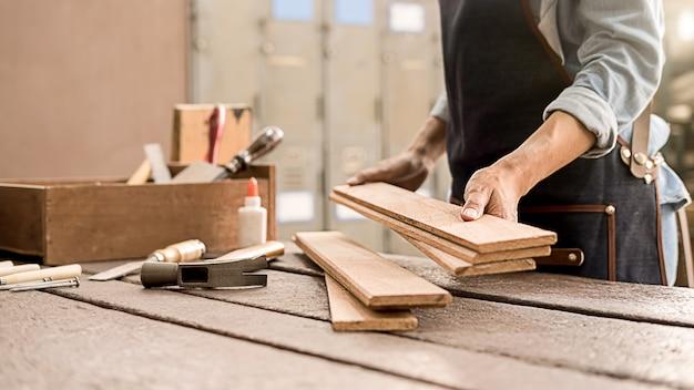 Carpentiere che lavora con l'attrezzatura sulla tavola di legno nel negozio di falegnameria.