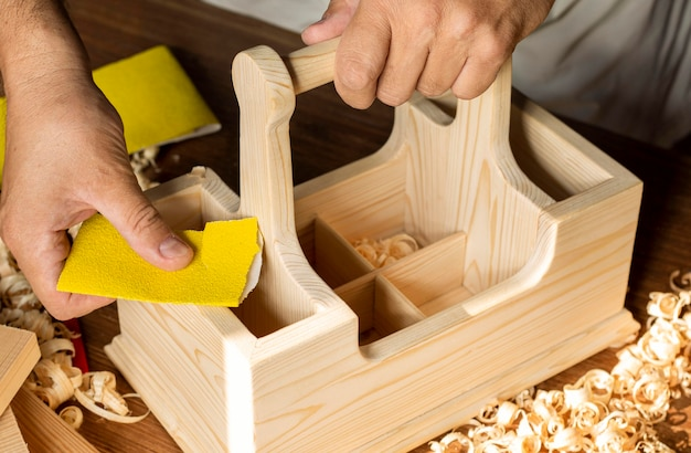 Carpentiere che lavora con carta vetrata gialla sulla scatola di legno