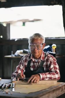 Carpentiere che lavora su legno nel negozio di falegnameria. l'uomo lavora in una falegnameria