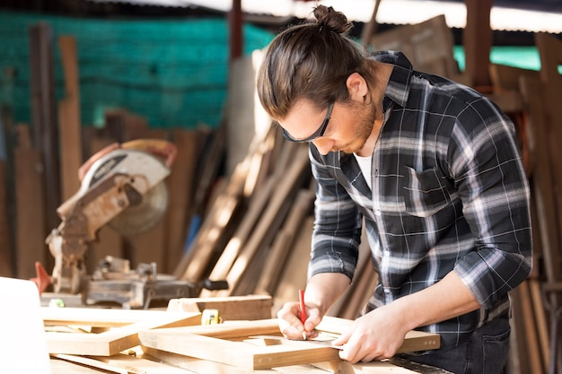 Carpentiere che lavora su macchine per la lavorazione del legno nel negozio di falegnameria. un uomo lavora in una falegnameria.