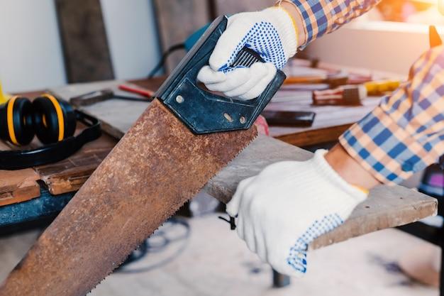Carpentiere che lavora su macchine per la lavorazione del legno in falegnameria.