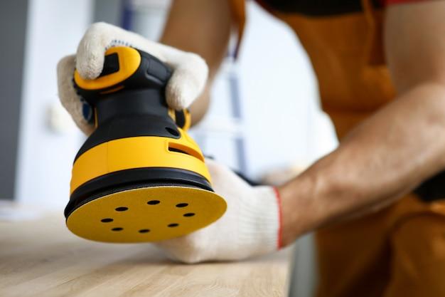 Il carpentiere lavora con l'albero con la levigatrice