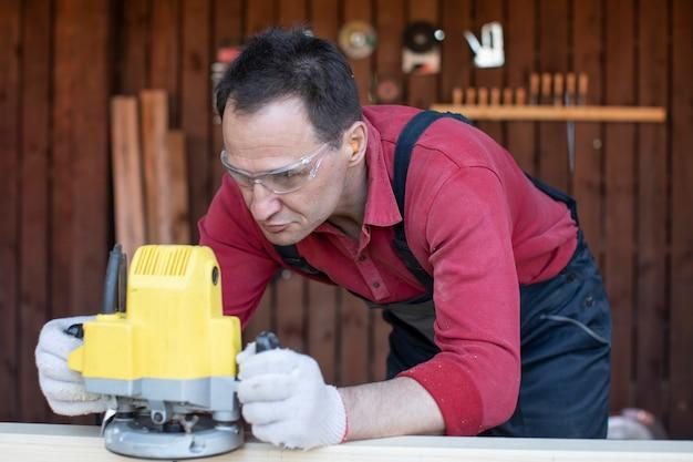 Falegname lavora sul pezzo in legno con utensile di fresatura al laboratorio di cottage si chiuda