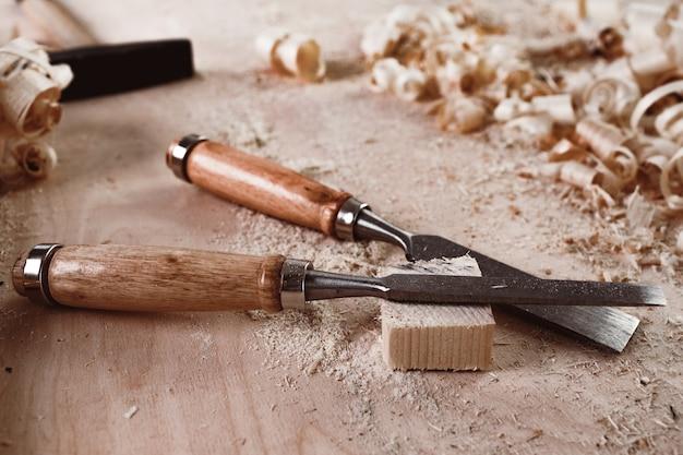I carpentieri scalpellano lo strumento per la lavorazione del legno sul desktop in officina