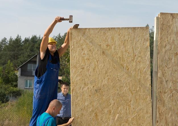 Carpentieri che montano pannelli a parete su una casa di nuova costruzione mentre lavorano nel cantiere in un sobborgo residenziale