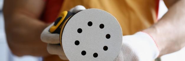 Le mani guantate dei carpentieri sostituiscono un pezzo di ricambio su una levigatrice riparazione e ristrutturazione di legno