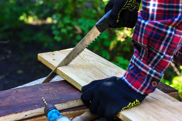 La falegnameria nel cortile di casa nonno sega una tavola di legno con una sega a mano