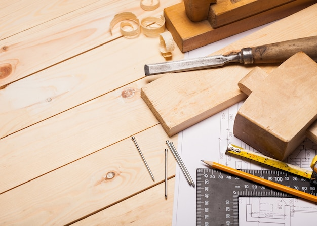 Strumenti di falegnameria con assi di legno e blueprint.