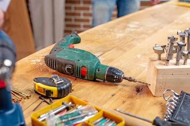 Il trapano dell'officina di carpenteria e altri strumenti si trovano sul tavolo