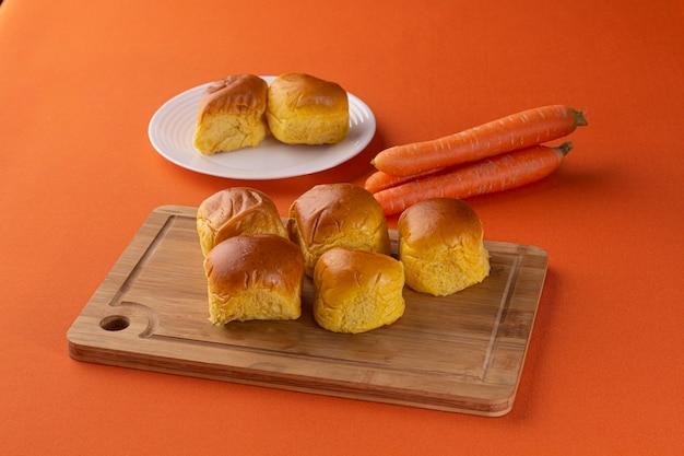 Pane alle carote sopra una tavola di legno e una zucca sullo sfondo su uno sfondo arancione