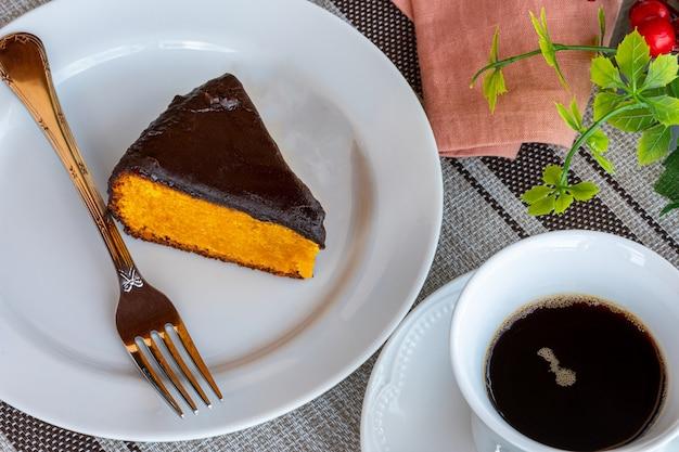Torta di carote con glassa al cioccolato, accompagnata da una tazza di caffè.
