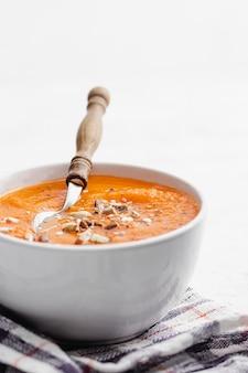 Zuppa di crema di carote in una ciotola bianca con tovagliolo di stoffa
