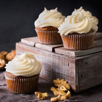 Cupcakes o muffin della carota con i dadi sul nero