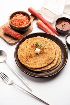 La carota o gajar ka paratha è un piatto del punjabi che è una focaccia indiana non lievitata fatta con farina integrale e carote. servito con ketchup e cagliata