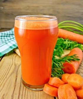 Succo di carota in un bicchiere alto, carote con verdure, un tovagliolo sullo sfondo di assi di legno