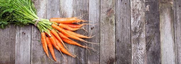 Mazzo di carote su uno sfondo di legno, stile rustico