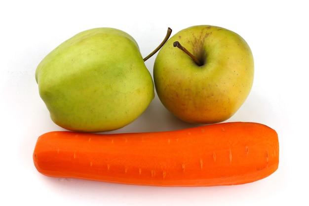 Carote e mele verdi su una superficie bianca