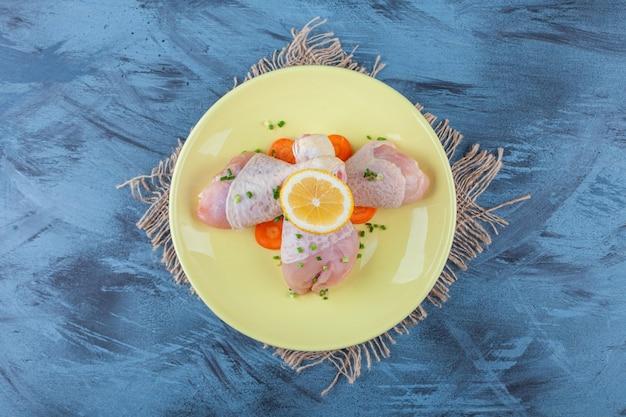 Carote, limone e bacchette su un piatto su un tovagliolo di tela da imballaggio, sulla superficie blu.