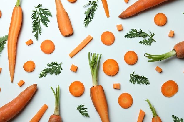 Carote, fette e foglie di carota sulla superficie bianca