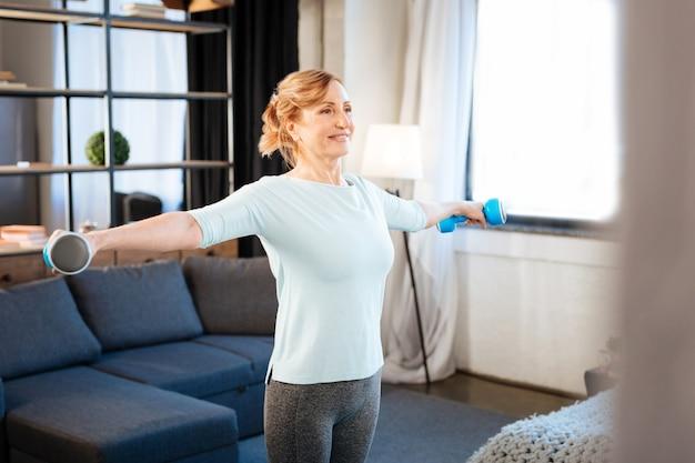 Portare manubri blu. donna matura attiva che indossa un abbigliamento sportivo comodo mentre fa esercizi con manubri in entrambe le mani