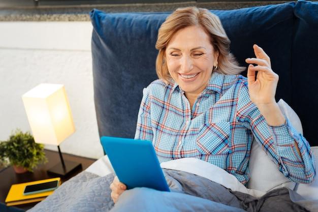 Porta tablet blu. piacevole donna con i capelli castani che ride mentre controlla il tablet al mattino