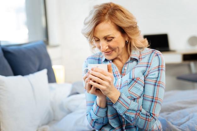 Tazza da trasporto. donna adulta positiva allegra che inizia la sua giornata con una tazza di bevanda calda mentre è seduta in camera da letto