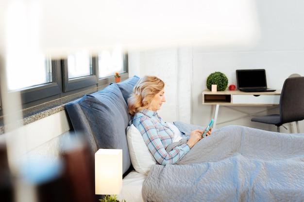 Portare il cellulare. donna adulta concentrata in pigiama blu brillante che si appoggia sul letto e cerca notizie sullo smartphone