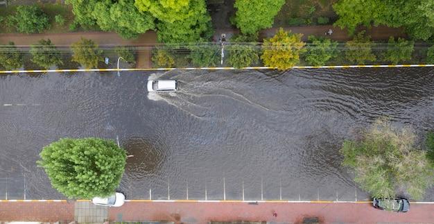 Le auto si stanno muovendo in una strada pesantemente allagata dopo un acquazzone anomalo.