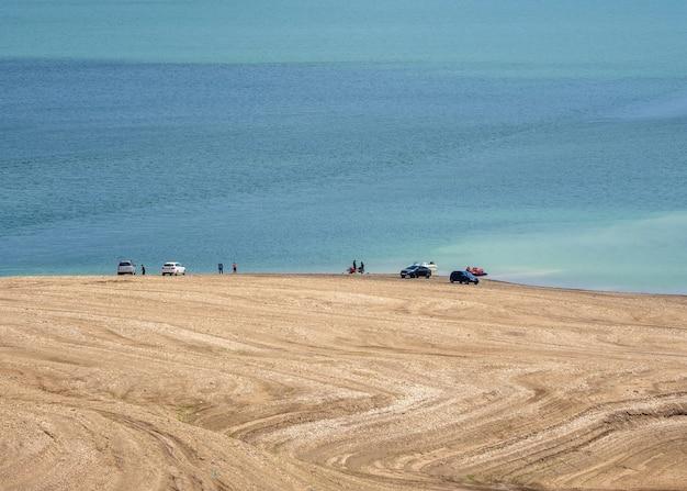 Auto sulla spiaggia. vista remota. serbatoio di sulak, daghestan. russia.