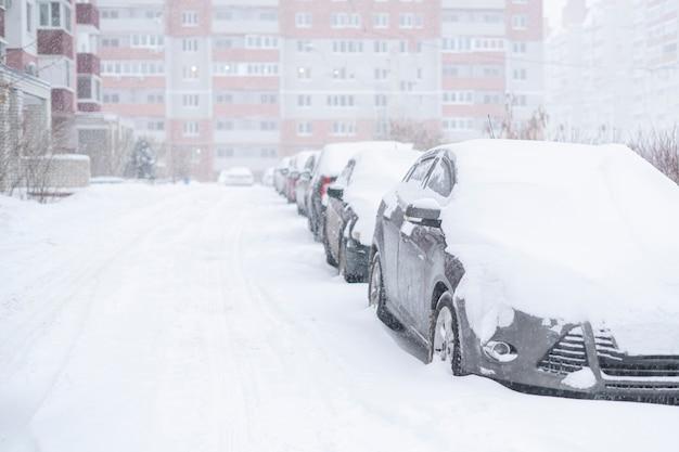Auto coperte di neve durante l'inverno, tempo tempestoso all'esterno