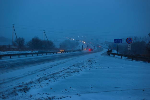 Le auto guidano sull'autostrada durante una tempesta di neve la sera.
