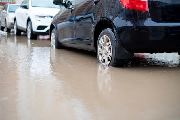Le auto si muovono nella strada dell'acqua, fuori dal disastro dell'alluvione