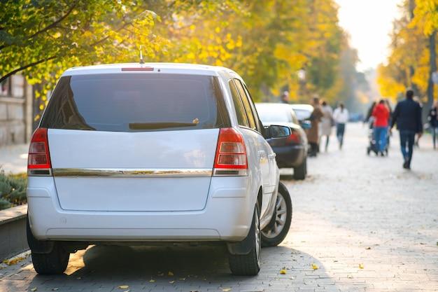 Auto parcheggiate in fila sul lato di una strada della città in una luminosa giornata autunnale con gente vaga che cammina sulla zona pedonale.