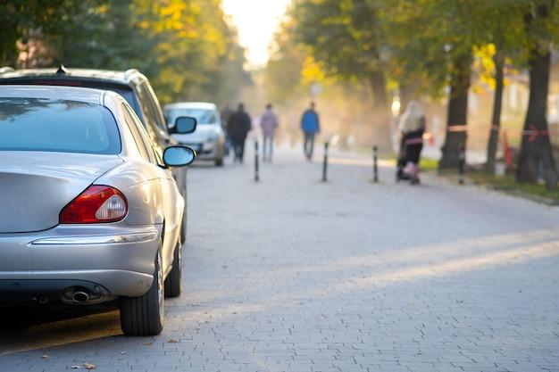 Auto parcheggiate in fila sul lato di una strada della città in una luminosa giornata autunnale con gente vaga che cammina sulla zona pedonale