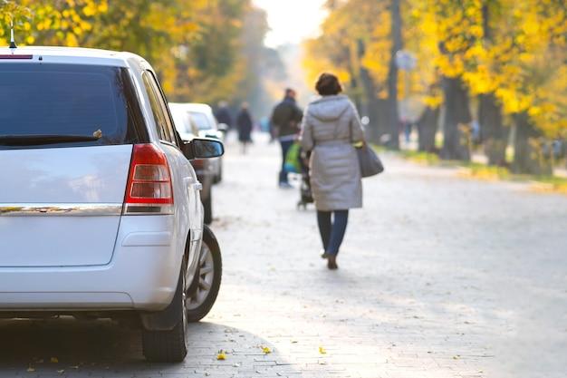Auto parcheggiate in fila su un lato di una strada cittadina in una luminosa giornata autunnale con persone sfocate che camminano sulla zona pedonale.