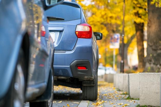 Auto parcheggiate in fila su un lato di una strada cittadina in una luminosa giornata autunnale.