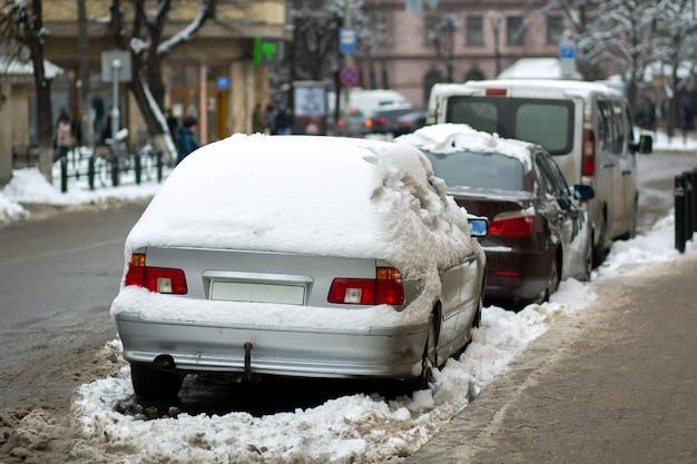 Auto parcheggiate su un lato della strada cittadina ricoperta di neve sporca in inverno.