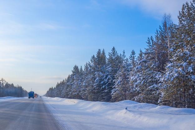 Le auto viaggiano su una strada invernale in una giornata di sole