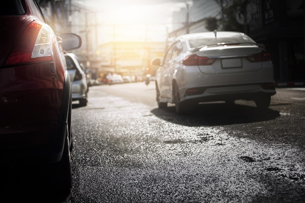 Auto su strada bagnata dopo la pioggia caduta con luce della sera in città, messa a fuoco selettiva. stagione delle piogge, sfondo del trasporto.
