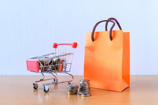 Supermercato del carrello e sacco di carta arancio sulla tavola di legno. concetto di acquisto