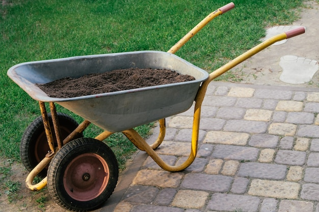 Carrello con terreno su lastre per pavimentazione accanto al prato verde. carriola con terra, per giardinaggio