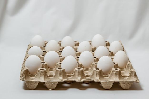 Scatola di cartone con uova bianche distanziate su sfondo bianco. concetto di regole di quarantena