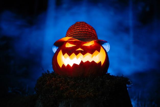 Faccia scolpita in zucca con candela all'interno sullo sfondo del concetto di ceppo di foresta nebbiosa ciao...