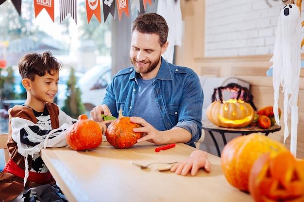 Intagliare la zucca. simpatico figlio raggiante che indossa il costume di halloween si sente allegro mentre intaglia la zucca con suo padre