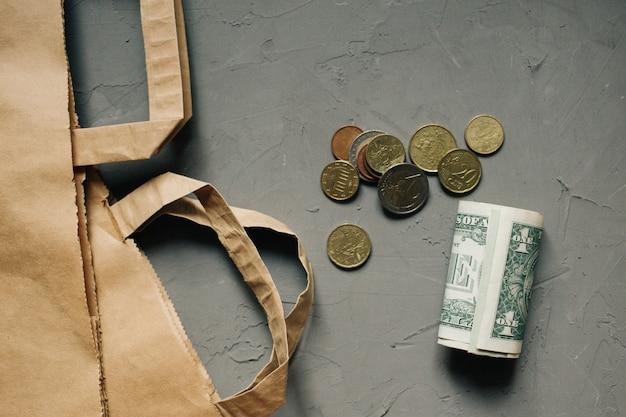 Denaro contante dollari, monete in euro con un pacchetto kraft su sfondo grigio.