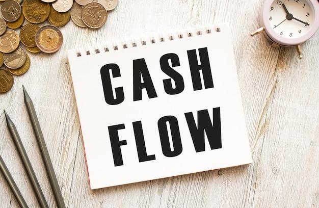 Testo flusso di cassa su un foglio di blocco note le monete sono matite sparse