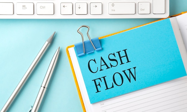 Testo cash flow su adesivo su sfondo blu con penna e tastiera