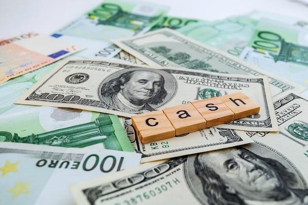 Iscrizione in contanti su cubi di legno sulla trama di dollari americani e banconote in euro