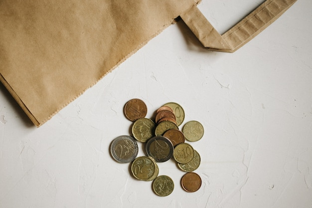 Denaro contante, monete in euro con un pacchetto kraft su sfondo bianco strutturato.